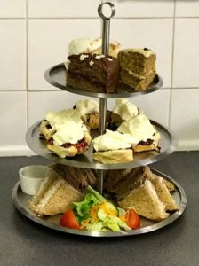 three tier cakestand filled with sandwiches , scones with jam and cream and cakes gift experience